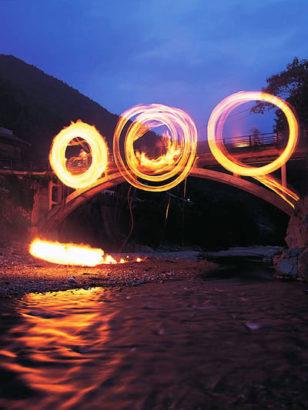 橋の上で火を回す 南牧 火とぼし お盆