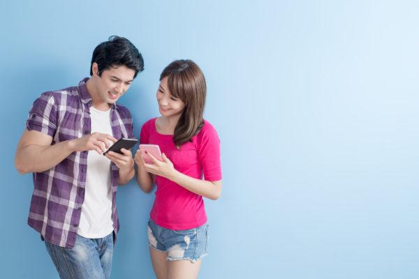 婚活サイト スマホを見せ合うカップル