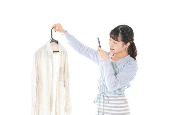 引越し不用品 服を撮影する女性イメージ
